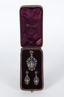 """8  -  <p><span class=""""object_title"""">Conjunto formado por broche-colgante Isabelino en plata, esmalte y perlas de aljófar con representación de mujer clásica en medallón central.</span></p>"""